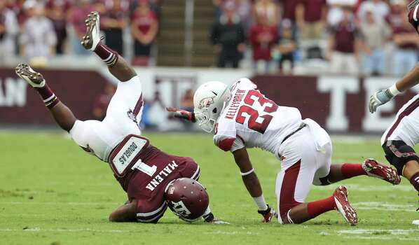 Texas A&M running back Ben Malena (1) flips after getting tackled by Arkansas cornerback Kaelon Kelleybrew (23) during the first half of a college football game at Kyle Field, Saturday, Sept. 29, 2012, in College Station. Photo: Karen Warren, Houston Chronicle / © 2012  Houston Chronicle