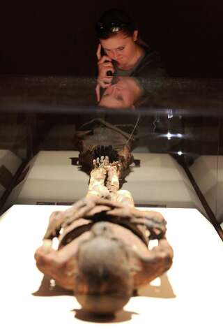 Lauren Asher of Denver views a mummy while listening to a guided audio tour of the Mummies of the World exhibit at the Witte Museum on Saturday, Sept. 29, 2012. The exhibit features 150 objects and specimens from South America, Europe, Asia, Oceania and Egypt. The exhibit will be open thru January 27, 2013. Photo: Kin Man Hui, San Antonio Express-News / ©2012 San Antonio Express-News