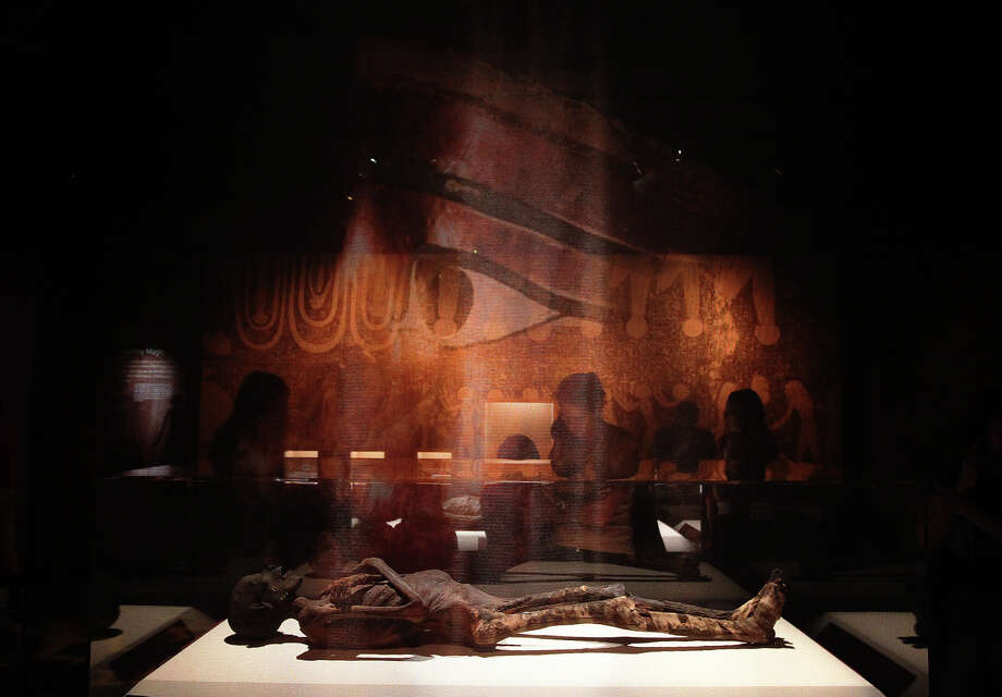 An image of a Egyptian carsophagus is projected on a transparent screen as exhibit guests view one of several mummies at the Mummies of the World exhibit at the Witte Museum on Saturday, Sept. 29, 2012. The exhibit features 150 objects and specimens from South America, Europe, Asia, Oceania and Egypt. The exhibit will be open thru January 27, 2013. Photo: Kin Man Hui, San Antonio Express-News / ©2012 San Antonio Express-News