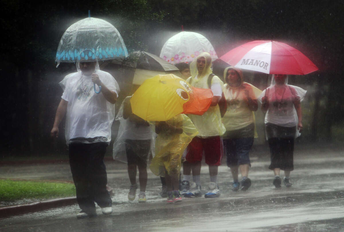 A group dons umbrellas and ponchos to shield themselves from a brief rain shower while at Brackenridge Park on Saturday, Sept. 29, 2012.