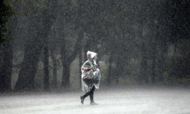 A park goer calmly makes her way back to her car during a brief rain shower at Brackenridge Park on Saturday, Sept. 29, 2012. Photo: Kin Man Hui, San Antonio Express-News / ©2012 San Antonio Express-News