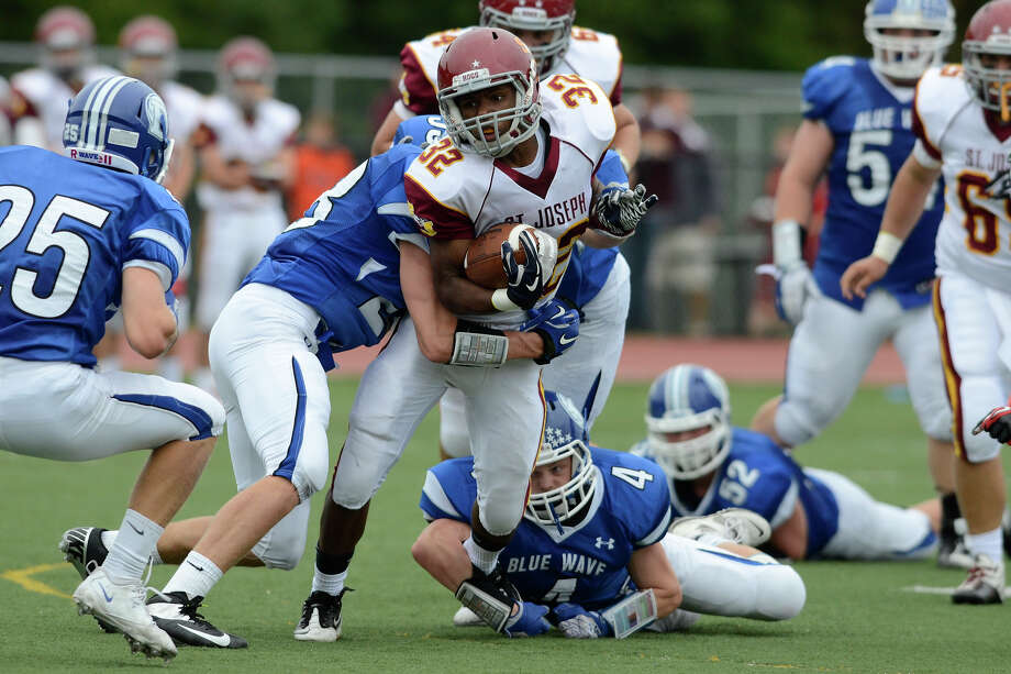 St. Joseph #32 Mufasha Abdul Basir battles the Darien defense as Darien High School hosts St. Joseph High School in varsity football in Darien, CT on Sept. 29, 2012. Photo: Shelley Cryan / Shelley Cryan for the Stamford Advocate/ freelance Shelley Cryan