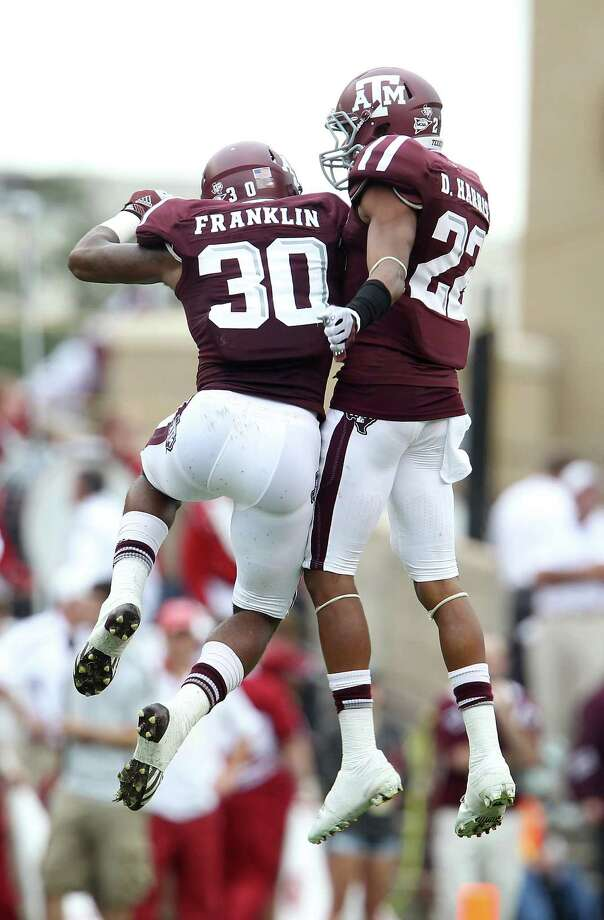 Texas A&M defensive back Johntel Franklin (30) and Texas A&M defensive back Dustin Harris (22) celebrate a turnover on downs during the fourth quarter of a college football game at Kyle Field, Saturday, Sept. 29, 2012, in College Station. Texas A&M beat Arkansas 58-10. Photo: Karen Warren, Houston Chronicle / © 2012  Houston Chronicle