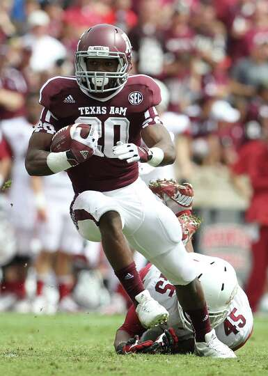 Texas A&M running back Trey Williams (20) gains yardage against Arkansas linebacker Alonzo Highsmith