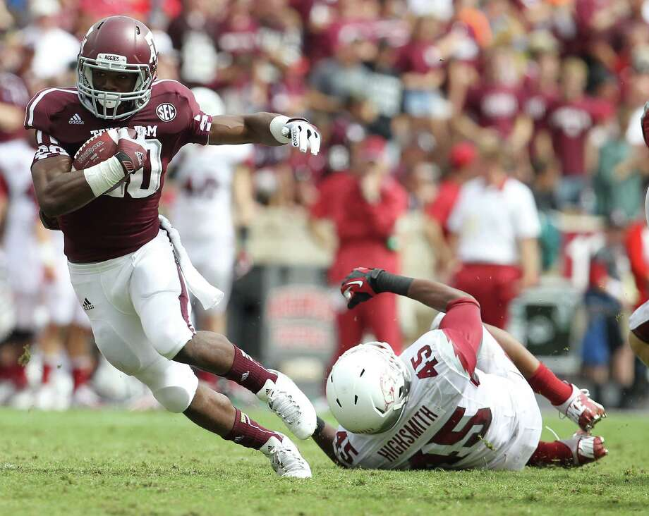 Texas A&M running back Trey Williams (20) gains yardage against Arkansas linebacker Alonzo Highsmith (45) during the third quarter of a college football game at Kyle Field, Saturday, Sept. 29, 2012, in College Station. Photo: Karen Warren, Houston Chronicle / © 2012  Houston Chronicle