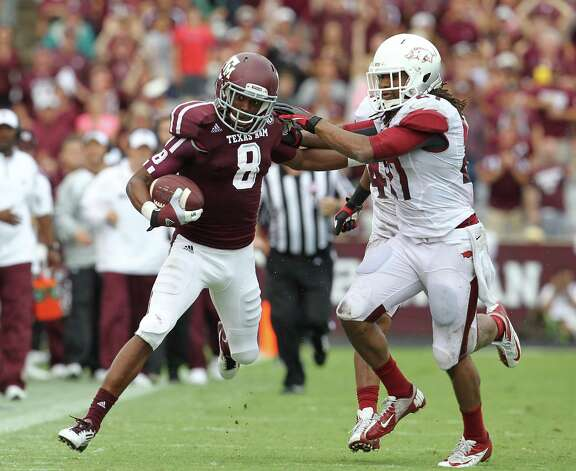Texas A&M wide receiver Thomas Johnson (8) gains 58 yards against Arkansas safety Alan Turner (27) during the third quarter of a college football game at Kyle Field, Saturday, Sept. 29, 2012, in College Station. Photo: Karen Warren, Houston Chronicle / © 2012  Houston Chronicle