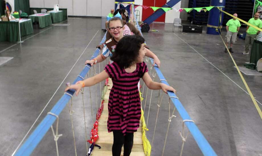 "Jacklyn Hernandez right front, and Madelyn Sloan Kinane walk across a rope span bridge during the San Jacinto chapter of the Girls Scouts of America ""The B.I.G Event"" (Believe in Girls) at the George R. Brown Convention Center. The Girls Scouts are celebrating their 100th anniversary in 2012. Photo: James Nielsen, Chronicle / © Houston Chronicle 2012"