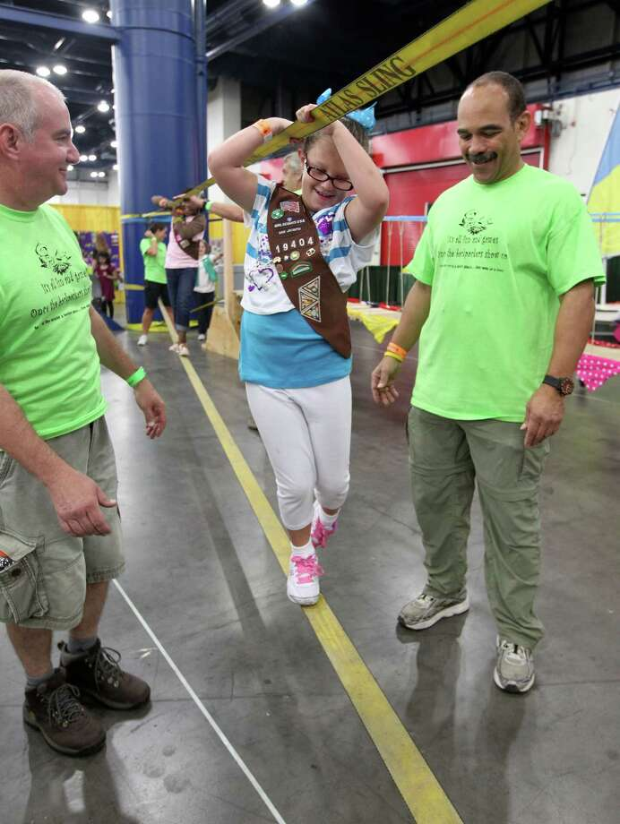 "Madelyn Sloan Kinane center, walks across a strap span as Rich Gold left, and Larry Cook standby during the San Jacinto chapter of the Girls Scouts of America ""The B.I.G Event"" (Believe in Girls) at the George R. Brown Convention Center. The Girls Scouts are celebrating their 100th anniversary in 2012. Photo: James Nielsen, Chronicle / © Houston Chronicle 2012"