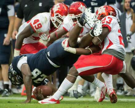 Rice running back Charles Ross (28) is upended by Houston defensive back Trevon Stewart (23) during the second quarter of the annual Bayou Bucket college football game at Reliant Stadium, Saturday, Sept. 29, 2012, in Houston. Photo: Smiley N. Pool, Houston Chronicle / © 2012  Houston Chronicle
