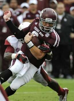 Texas A&M quarterback Johnny Manziel (right) is tackled by Arkansas 's A.J. Turner during the first half Saturday, Sept. 29, 2012, in College Station. (Pat Sullivan / Associated Press)
