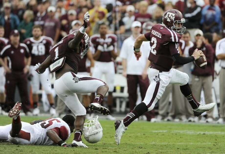 Texas A&M quarterback Johnny Manziel (2) breaks away from Arkansas defender Alonzo Highsmith (45) as teammate Ben Malena (1) hops over a helmet in the first half Saturday, Sept. 29, 2012, in College Station. (Pat Sullivan / Associated Press)