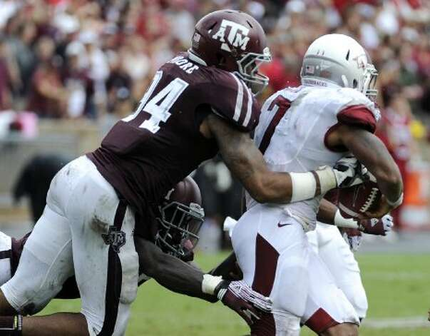 Texas A&M defensive lineman Damontre Moore (94) knocks the ball loose from Arkansas running back Knile Davis (7) during the third quarter Saturday, Sept. 29, 2012, in College Station. A&M's Tramain Jacobs recovered the ball and scored a touchdown. (Pat Sullivan / Associated Press)