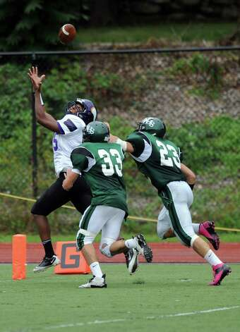 Westhill's Yveson Cassamajor makes a catch and a touchdown as he is followed by Norwalk's James Marino, left, and Daniel Jakab, right, during Saturday's football game against Norwalk High School at Westhill High School on September 29, 2012. Photo: Lindsay Niegelberg / Stamford Advocate