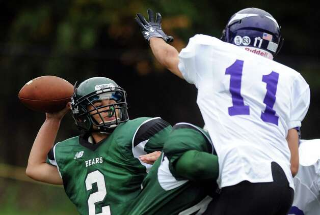 Norwalk's Andy Lovo throws a pass as Westhill's Nick Jiminez reaches to block during Saturday's football game at Westhill High School on September 29, 2012. Photo: Lindsay Niegelberg / Stamford Advocate