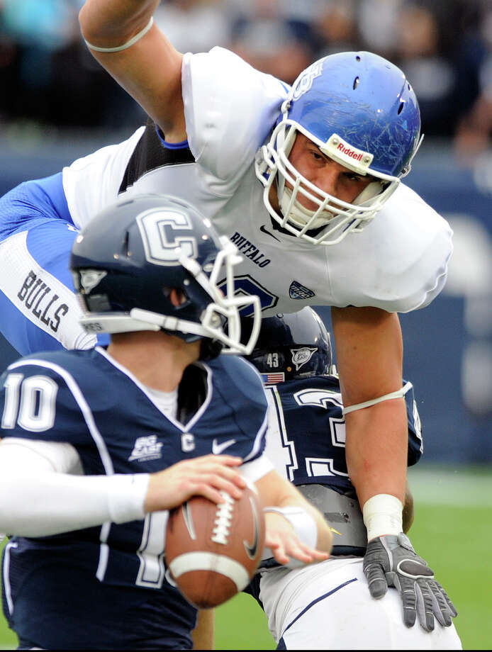 Connecticut's Chandler Whitmer, foreground, is pressured by Buffalo's Kristjan Sokolo during the first half of their NCAA college football game in East Hartford, Conn., on Saturday, Sept. 29, 2012. (AP Photo/Fred Beckham) Photo: Fred Beckham, Associated Press / FR153656 AP