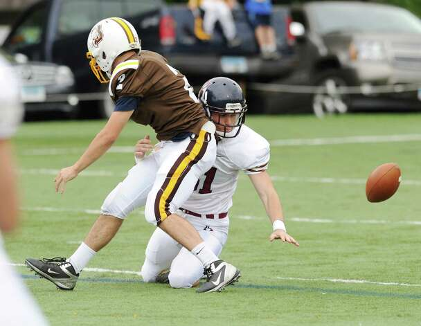 Kyle Malley # 51 of Avon Old Farms School looks for the ball after forcing a fumble on Billy O'Malley, left,  # 2 of Brunswick, during high school football game between Brunswick School and Avon Old Farms School at Brunswick in Greenwich, Saturday afternoon, Sept. 29, 2012. Brunswick recovered the ball. Photo: Bob Luckey / Greenwich Time