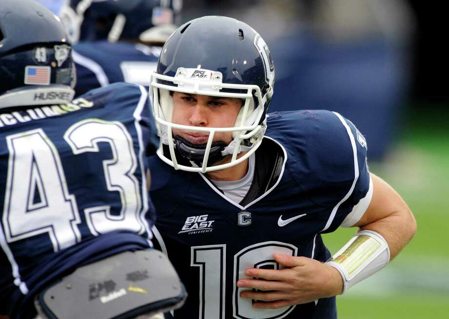 Connecticut's Chandler Whitmer, right, hands the ball off to Lyle McCombs during the second half of Connecticut's 24-17 victory over Buffalo in their NCAA football game in East Hartford, Conn., on Saturday, Sept. 29, 2012. (AP Photo/Fred Beckham) Photo: Fred Beckham, Associated Press / FR153656 AP
