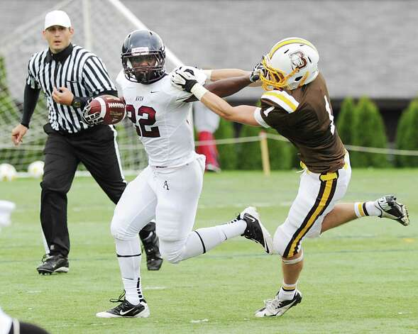 Avon Old Farms running back Mickoy Nichol, # 22, face-masks Brunswick's Sam Fraser, right,  # 1, on a running play during the high school football game between Brunswick School and Avon Old Farms School at Brunswick in Greenwich, Saturday afternoon, Sept. 29, 2012. A face-masking penalty was called on the play. Photo: Bob Luckey / Greenwich Time