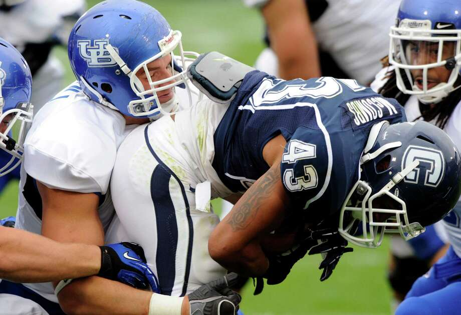 Buffalo's Kristjan Sokoli, left, tackles Connecticut's Lyle McCombs during the first half of Connecticut's 24-17 victory in their NCAA football game in East Hartford, Conn., on Saturday, Sept. 29, 2012. (AP Photo/Fred Beckham) Photo: Fred Beckham, Associated Press / FR153656 AP