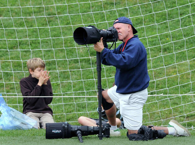 Photographer Dan Burns works from the endzone during the high school football game between Brunswick School and Avon Old Farms School at Brunswick in Greenwich, Saturday afternoon, Sept. 29, 2012. Photo: Bob Luckey / Greenwich Time