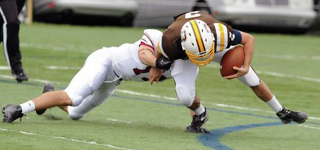 At right, Billy O'Malley # 2 of Brunswick attempts to get away from an Avon Old Farms defender on a running play during the high school football game between Brunswick School and Avon Old Farms School at Brunswick in Greenwich, Saturday afternoon, Sept. 29, 2012. Photo: Bob Luckey / Greenwich Time