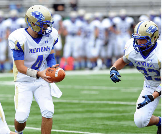 Newtown QB Andrew Tarantino prepares to hand off the ball to #33 Nicholas Rubino, during football action against Stratford in Stratford, Conn. on Saturday September 29, 2012. Photo: Christian Abraham / Connecticut Post