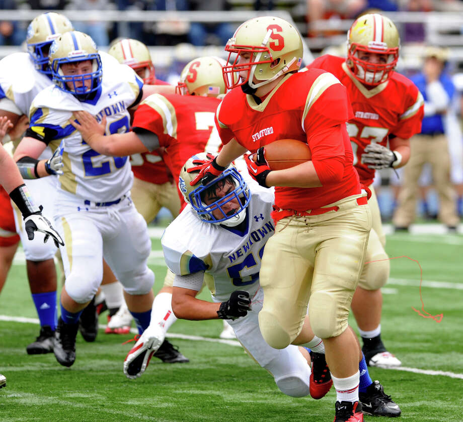 Stratford's #3 Sam Breiner pushes off Newtown's #52 Nicholas Norberg as he carries the ball, during football action in Stratford, Conn. on Saturday September 29, 2012. Photo: Christian Abraham / Connecticut Post