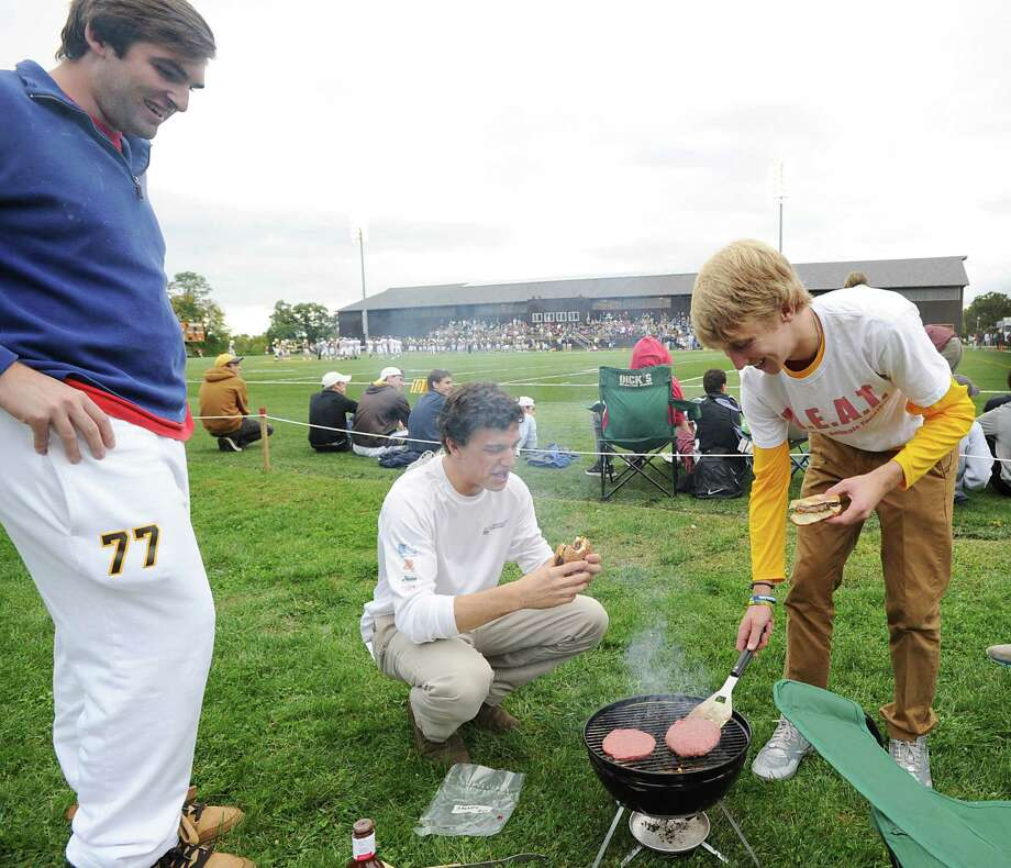 At right Alex Baldock, 17, a Brunswick School senior, flips the burgers on the grill during the high school football game between Brunswick School and Avon Old Farms School at Brunswick in Greenwich, Saturday afternoon, Sept. 29, 2012. The game was Homecoming. Photo: Bob Luckey / Greenwich Time