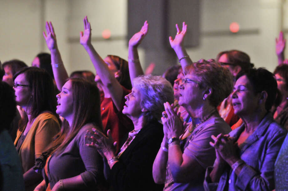 Bathed in stage lighting, women pray and sing at the Women of Joy conference at the Convention Center. Continuing today, it's drawn participants from across the region and is one of nine such events being held across the country. Photo: Robin Jerstad,  For The Express-News