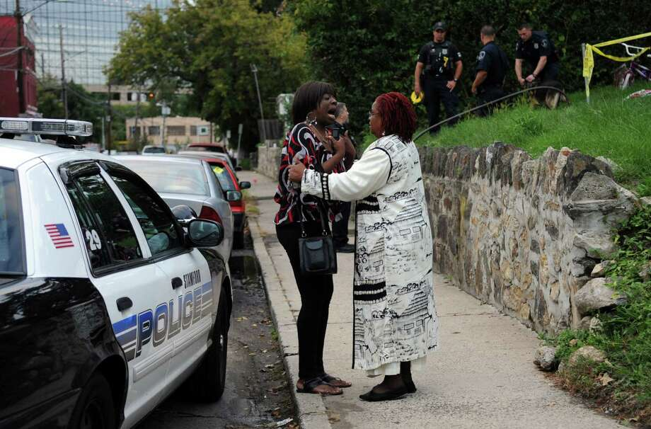 A woman identified as the wife of a man shot in the leg at 284 Greenwich Avenue is comforted by her neighbor, Emily Collington, Saturday, September 29, 2012. Photo: Lindsay Niegelberg / Stamford Advocate