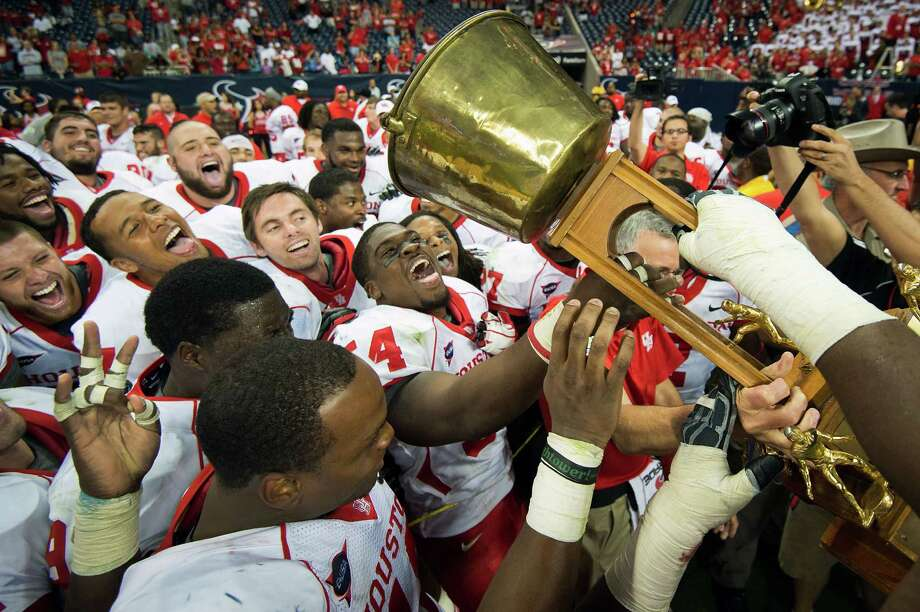 UH 35, Rice 14Houston players celebrate with the Bayou Bucket trophy after defeating crosstown rival Rice in a college football game at Reliant Stadium, Saturday, Sept. 29, 2012, in Houston. Houston won the game 35-14. Photo: Smiley N. Pool, Houston Chronicle / © 2012  Houston Chronicle