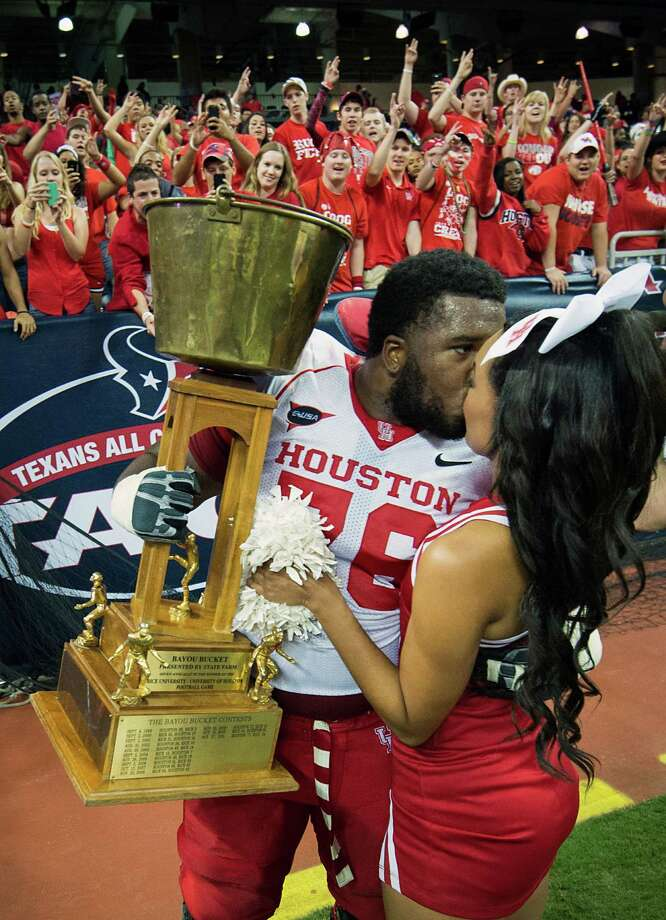 Houston offensive linesman Jacolby Ashworth gets a kiss from a cheerleader as he takes a victory lap with the Bayou Bucket trophy after the Cougars defeated crosstown rival Rice in a college football game at Reliant Stadium, Saturday, Sept. 29, 2012, in Houston. Houston won the game 35-14. Photo: Smiley N. Pool, Houston Chronicle / © 2012  Houston Chronicle