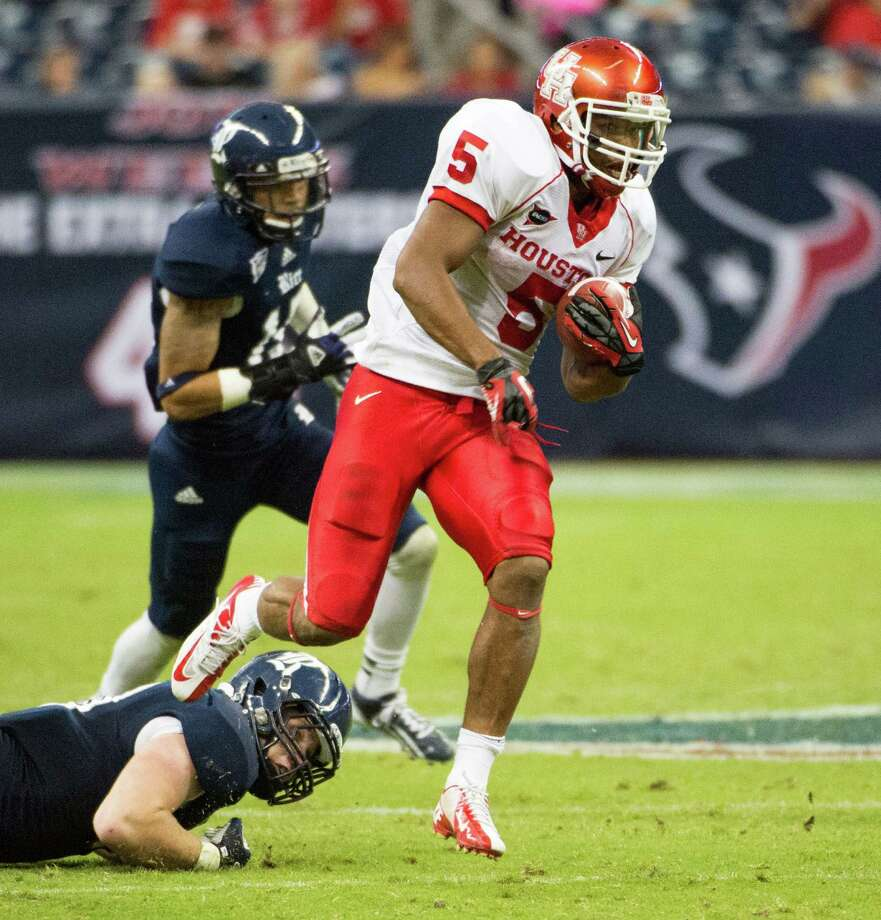 Houston running back Charles Sims (5) breaks a tackle on a 47-yard touchdown run during the third quarterof the annual Bayou Bucket college football game against Rice at Reliant Stadium, Saturday, Sept. 29, 2012, in Houston. Houston won the game 35-14. Photo: Smiley N. Pool, Houston Chronicle / © 2012  Houston Chronicle