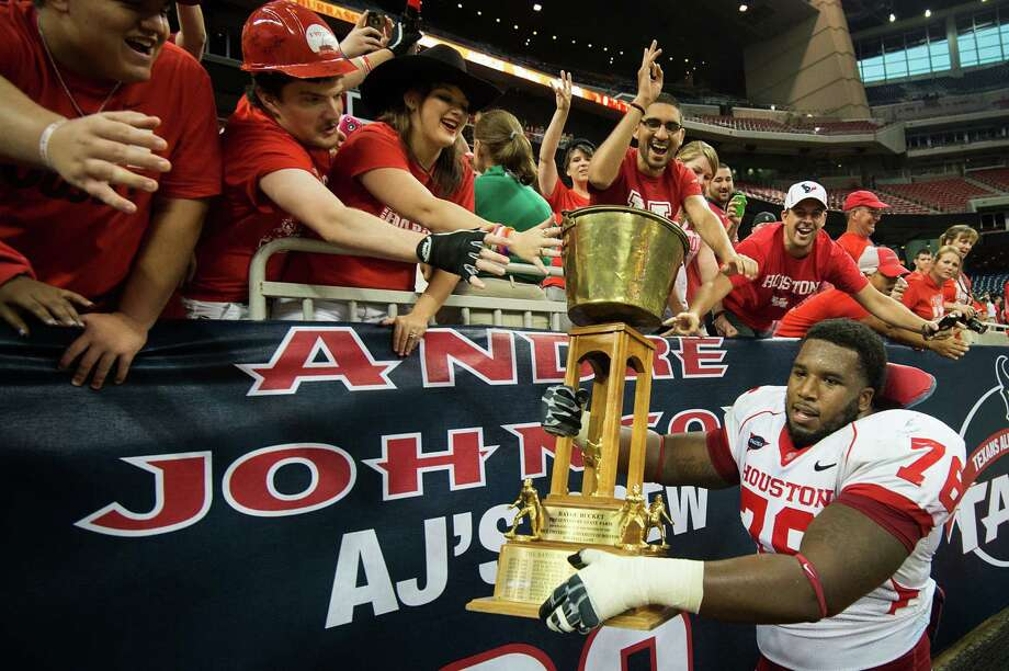 Houston offensive linesman Jacolby Ashworth takes a victory lap with the Bayou Bucket trophy after defeating crosstown rival Rice in a college football game at Reliant Stadium, Saturday, Sept. 29, 2012, in Houston. Houston won the game 35-14. Photo: Smiley N. Pool, Houston Chronicle / © 2012  Houston Chronicle