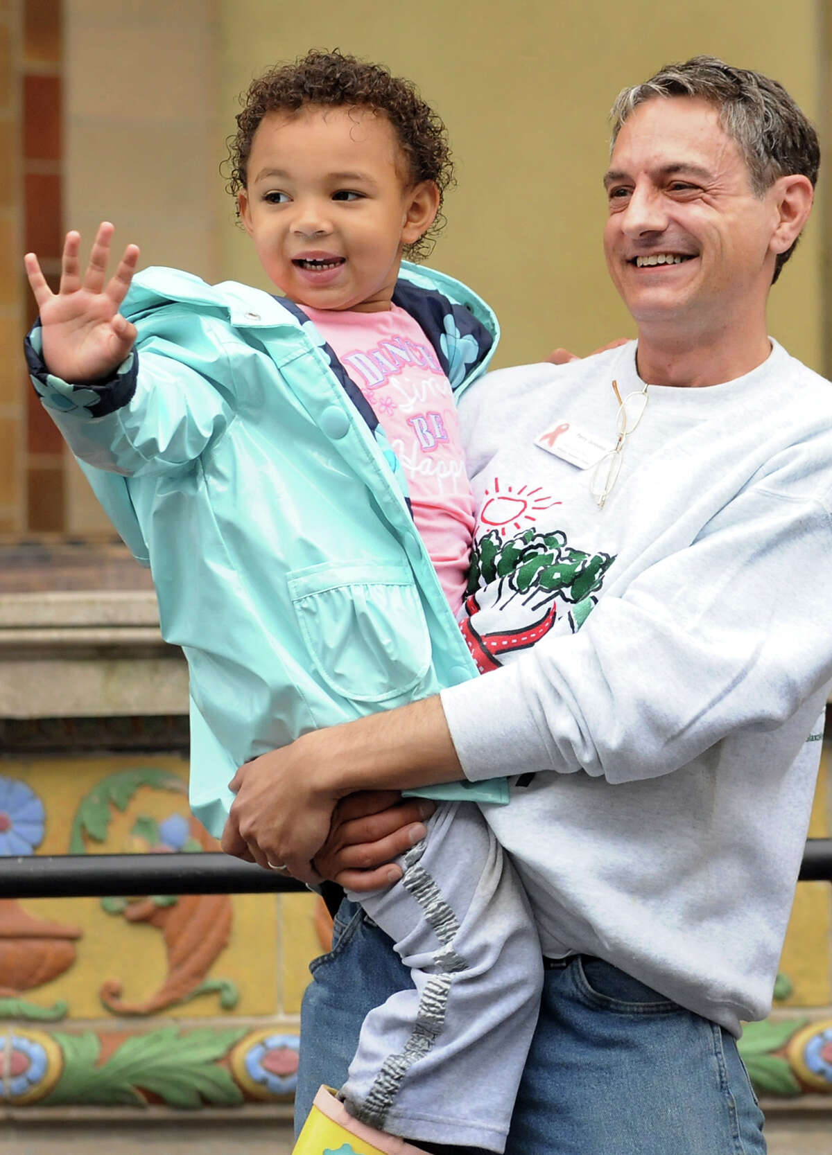 Perry Junjulas, executive director of the Damien Center, right, holds his granddaughter Angie Ward-Green, 4, as she waves from the stage during the annual AIDSWalk on Saturday, Sept. 29, 2012, at Washington Park in Albany, N.Y. Junjulas has been living with AIDS since 1995. This event helps Capital Region organizations provide prevention, education and support services for those living with HIV and AIDS. (Cindy Schultz / Times Union)