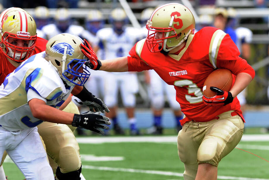 Stratford's #3 Sam Breiner reaches out to push away Newtown's #52 Nicholas Norberg as he carries the ball, during football action in Stratford, Conn. on Saturday September 29, 2012. Photo: Christian Abraham / Connecticut Post