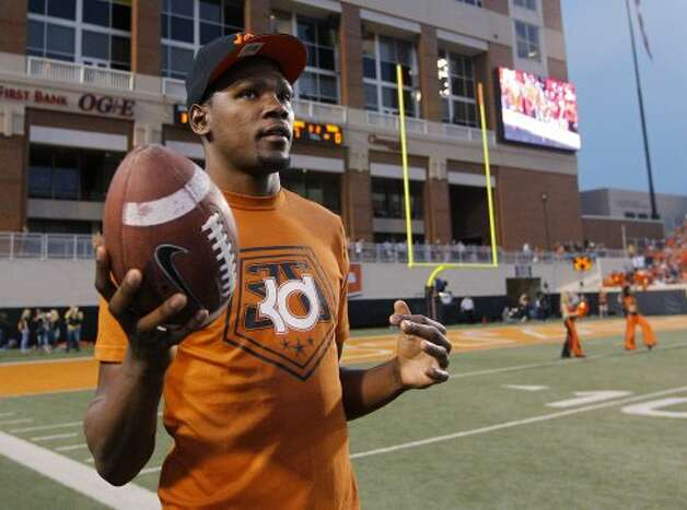 Oklahoma City Thunder's Kevin Durant, who attended Texas, tosses a football around on the sidelines during the first quarter of an NCAA college football game between Oklahoma State and Texas in Stillwater, Okla., Saturday, Sept. 29, 2012. (Sue Ogrocki / Associated Press)