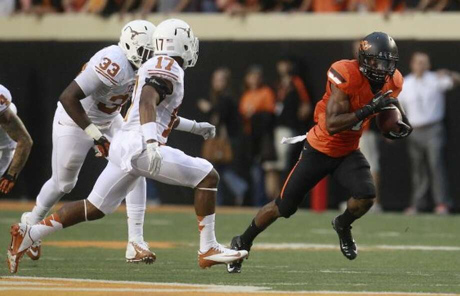 Oklahoma State running back Joseph Randle (1) eludes Texas' Steve Edmond (33) and Adrian Phillips (17) and takes off on a 69-yard touchdown run in the first quarter in Stillwater, Okla., Saturday, Sept. 29, 2012.  (Sue Ogrocki / Associated Press)