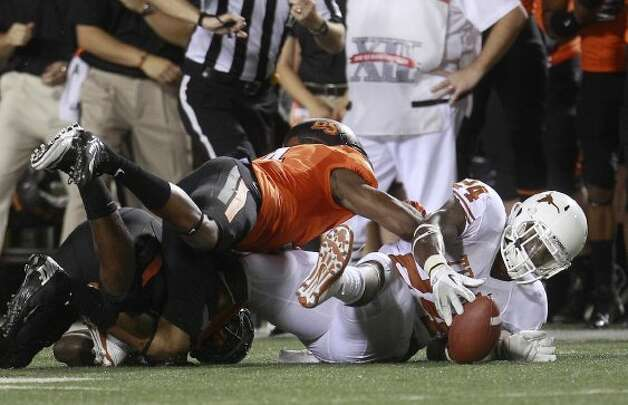 Texas running back Joe Bergeron (24) recovers his own fumble as Oklahoma State cornerback Justin Gilbert (4) reaches for it during the second quarter in Stillwater, Okla., Saturday, Sept. 29, 2012. (Sue Ogrocki / Associated Press)