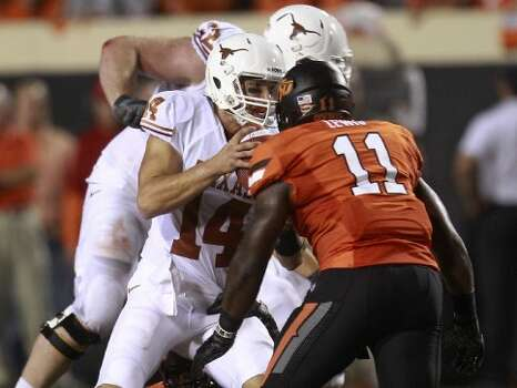 Oklahoma State linebacker Shaun Lewis (11) moves in to sack Texas quarterback David Ash (14) during the second quarter in Stillwater, Okla., Saturday, Sept. 29, 2012. (Sue Ogrocki / Associated Press)