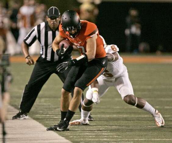 Wide receiver David Glidden (6) of Oklahoma State tries to stay in bounds under pressure from cornerback Quandre Diggs (6) of Texas on Sept. 29, 2012 at Boone Pickens Stadium in Stillwater, Oklahoma. (Brett Deering / Getty Images)