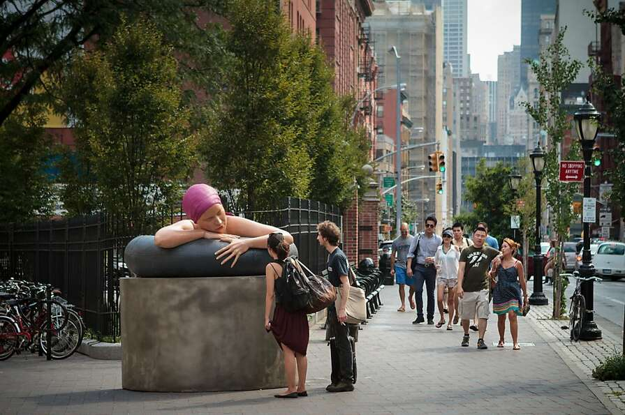 Passers-by inspect public art at Lafayette and Spring streets in New York's district of Nolita, a