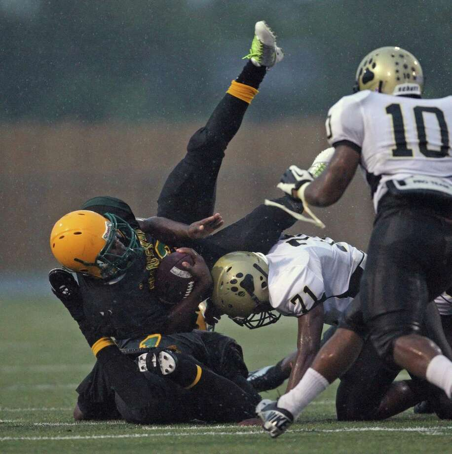 Sharpstown's Jerrod Taylor (2) is flipped over by North Forest's Anthony Davis (71) during the first half of a high school football game, Saturday, September 29, 2012 at Butler Stadium in Houston, TX. Photo: Eric Christian Smith, For The Chronicle