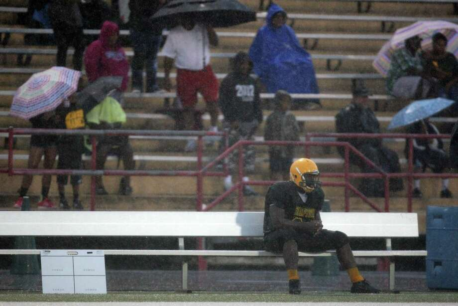 Trailing 34-0 in the second quarter and during a rainstorm, Sharpstown's Spencer Cook finds time to himself on the bench during a high school football game against North Forest, Saturday, September 29, 2012 at Butler Stadium in Houston, TX. Photo: Eric Christian Smith, For The Chronicle