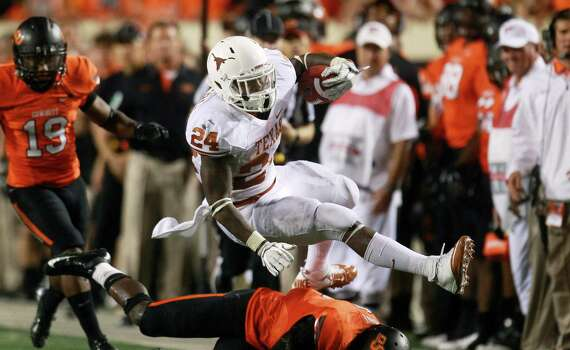 Texas running back Joe Bergeron (24) tries to get past Oklahoma State safety Daytawion Lowe, bottom, during the fourth quarter of an NCAA college football game in Stillwater, Okla., Saturday, Sept. 29, 2012. Texas won 41-36. AP Photo/Sue Ogrocki) Photo: Sue Ogrocki, Associated Press / AP
