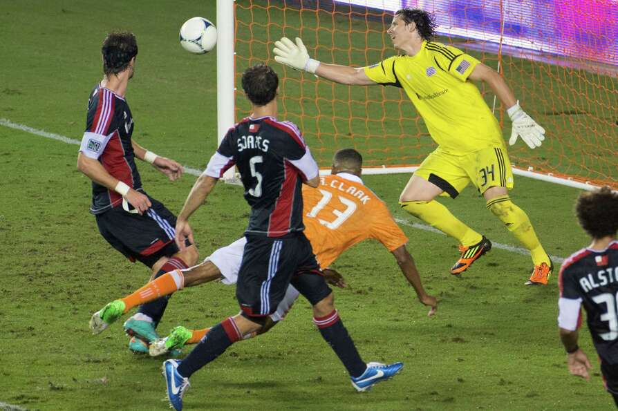 A header by Houston Dynamo midfielder Ricardo Clark, bottom, gets past New England Revolution goalke