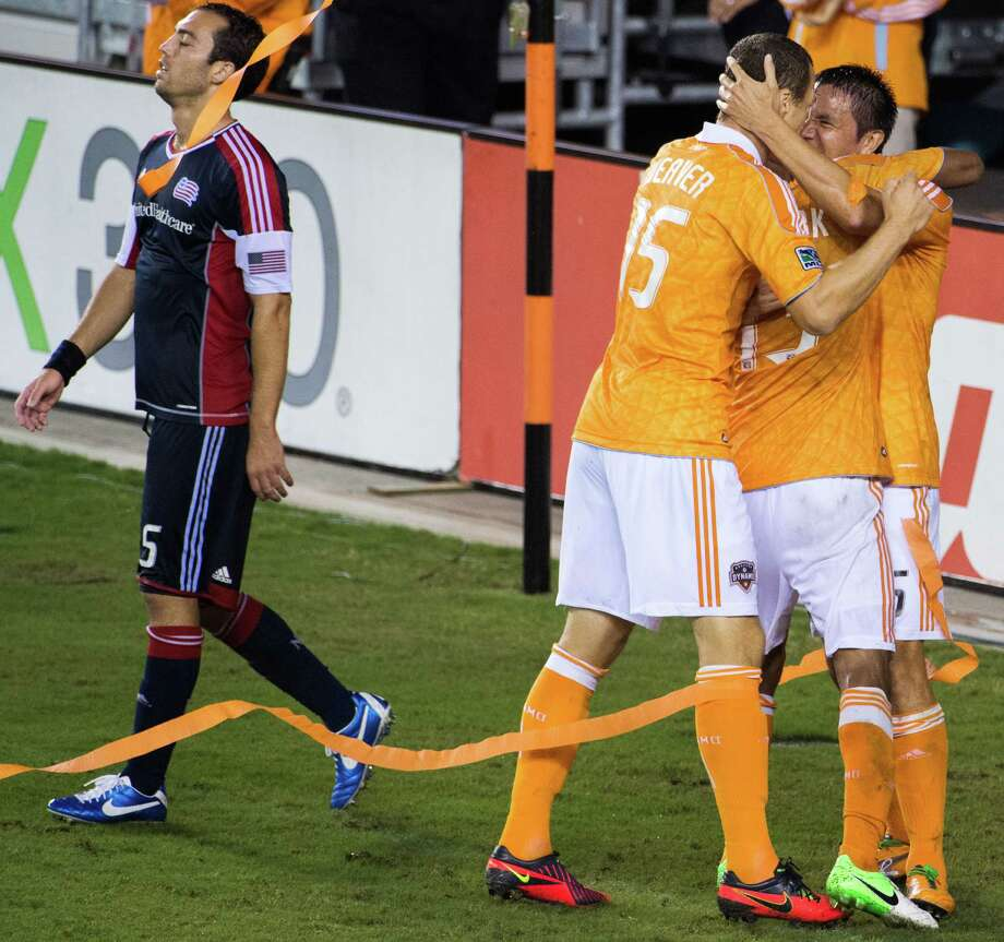 New England Revolution defender A.J. Soares (5) walks away as Houston Dynamo forward Cam Weaver (15), midfielder Ricardo Clark (13) and forward Brian Ching (25) celebrate after Clark scored in the 77th minute during the second half on Saturday, Sept. 29, 2012, at BBVA Compass Stadium in Houston. The Dynamo won the game 2-0. Photo: Smiley N. Pool, Houston Chronicle / © 2012  Houston Chronicle