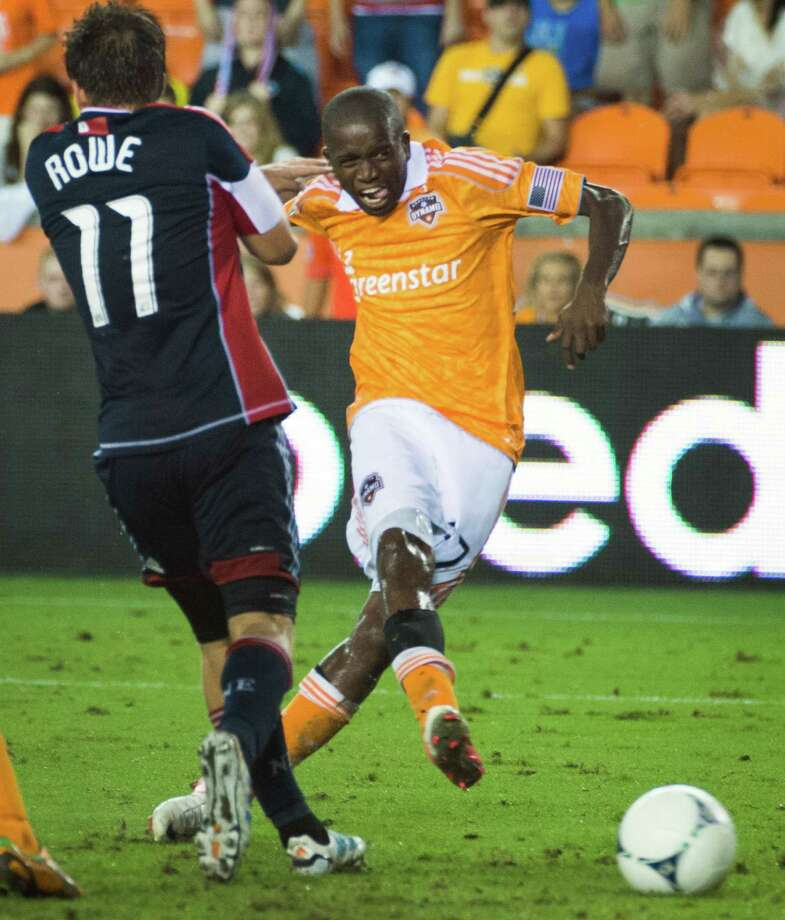 Houston Dynamo midfielder Boniek Garcia (27) makes a shot past New England Revolution midfielder Kelyn Rowe (11) to score a goal in the 93rd minute of an MLS soccer match on Saturday, Sept. 29, 2012, at BBVA Compass Stadium in Houston. The Dynamo won the game 2-0. Photo: Smiley N. Pool, Houston Chronicle / © 2012  Houston Chronicle