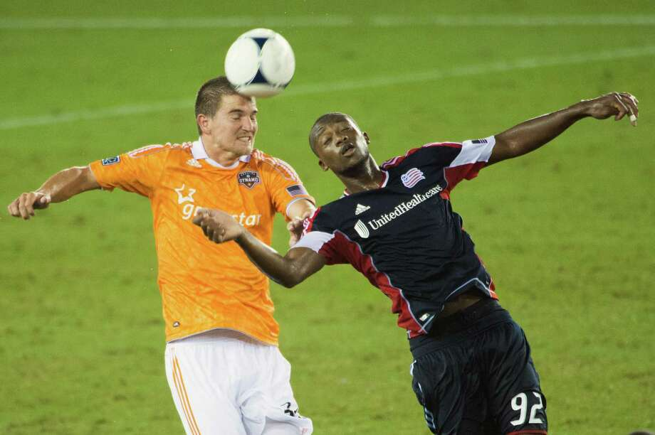 Houston Dynamo defender Bobby Boswell (32) wins a header from New England Revolution forward Dimitry Imbongo Boele (92) during the second half on Saturday, Sept. 29, 2012, at BBVA Compass Stadium in Houston. The Dynamo won the game 2-0. Photo: Smiley N. Pool, Houston Chronicle / © 2012  Houston Chronicle