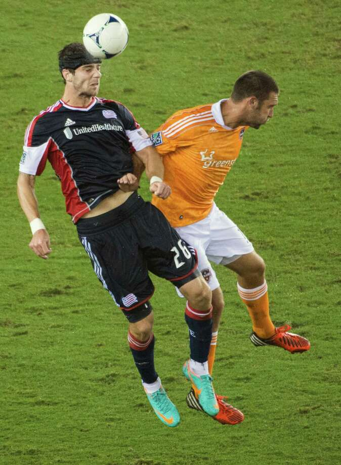 New England Revolution midfielder Stephen McCarthy (26) wins a header from Houston Dynamo forward Will Bruin (12) on Saturday, Sept. 29, 2012, at BBVA Compass Stadium in Houston. Photo: Smiley N. Pool, Houston Chronicle / © 2012  Houston Chronicle